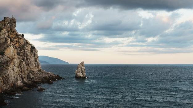 Rocce e mare con cielo serale.
