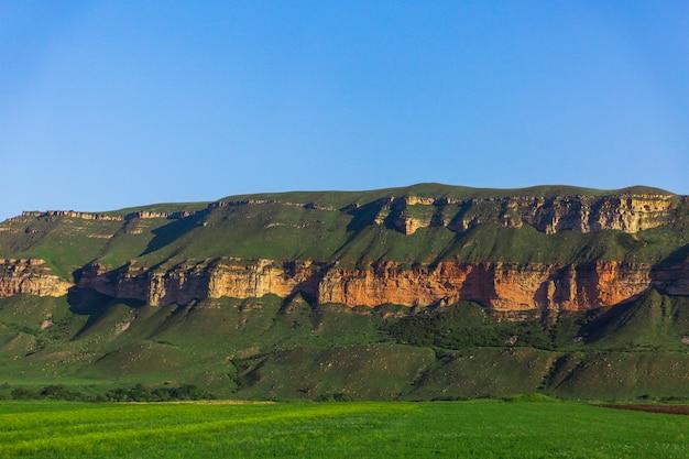 Rocce con erba verde su sfondo blu cielo. splendido paesaggio di natura selvaggia. terreno edificabile