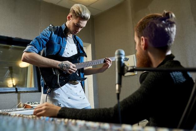 Chitarrista rockstar che compone una nuova canzone con il produttore