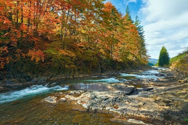 Rocky autumn mountain river con piccole cascate
