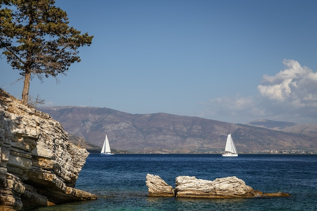 Spiaggia rocciosa nell'isola di corfù grecia barche a vela yacht nel mare limpido acqua blu