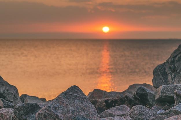 Spiaggia rocciosa con sfondo tramonto.