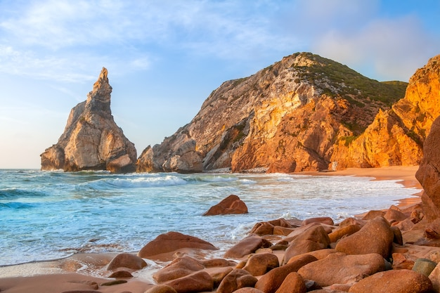 Costa rocciosa dell'oceano atlantico. piccola spiaggia deserta. il tramonto ha dipinto le pietre d'oro