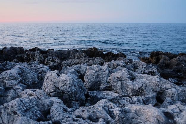 Costa rocciosa file di pietre taglienti, onde che si infrangono. paesaggi maestosi