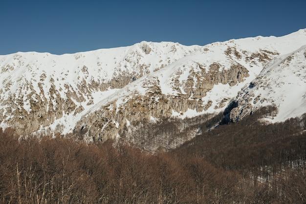 Paesaggio delle montagne rocciose ricoperte di neve con cielo blu sullo sfondo. natura meravigliosa.