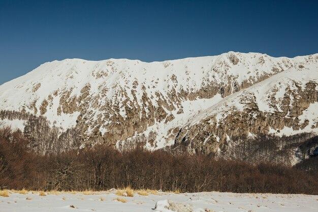 Paesaggio delle montagne rocciose ricoperte di neve con cielo blu sullo sfondo.