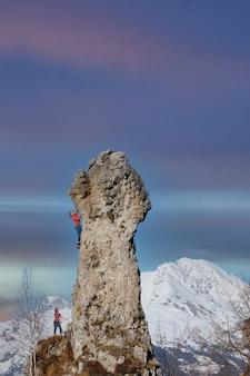 Picco roccioso con un paio di alpinisti in corde