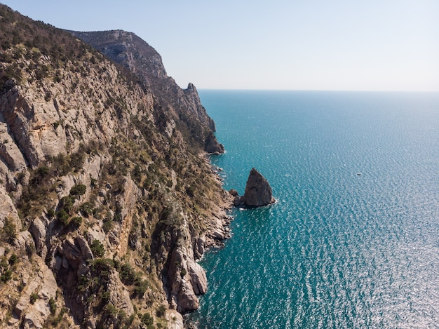 Vista dall'alto della spiaggia rocciosa. enormi scogliere ripide e oceano infinito. libertà e viaggio.