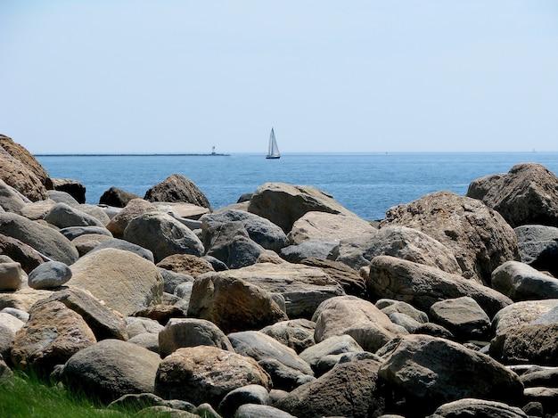 Costa rocciosa con barca a vela sullo sfondo costa del parco statale della spiaggia di hammonasset