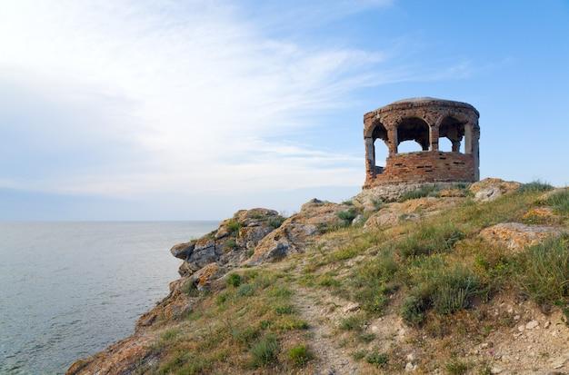 Costa rocciosa estiva e capo con padiglione su sfondo blu cielo