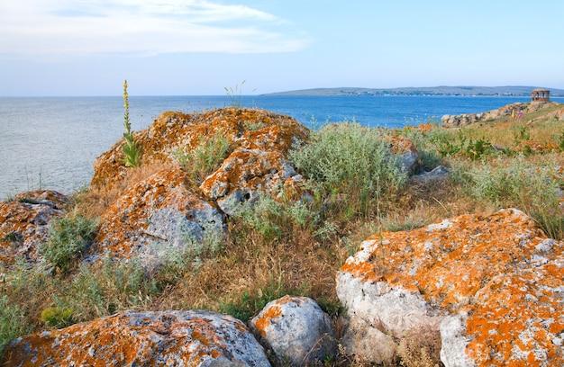 Costa rocciosa estiva e promontorio con padiglione