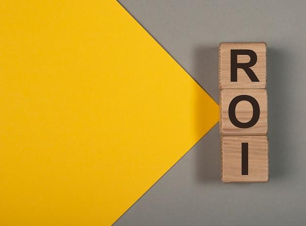 Testo di ritorno dell'investimento roi su cubi di legno su banner con spazio di copia