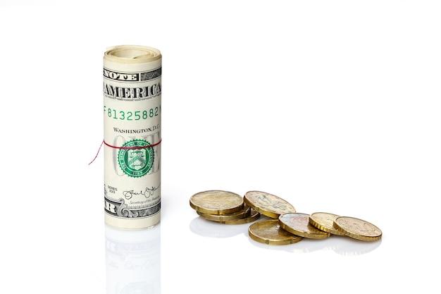 Rotolo di dollari americani accanto a monete in euro sparse