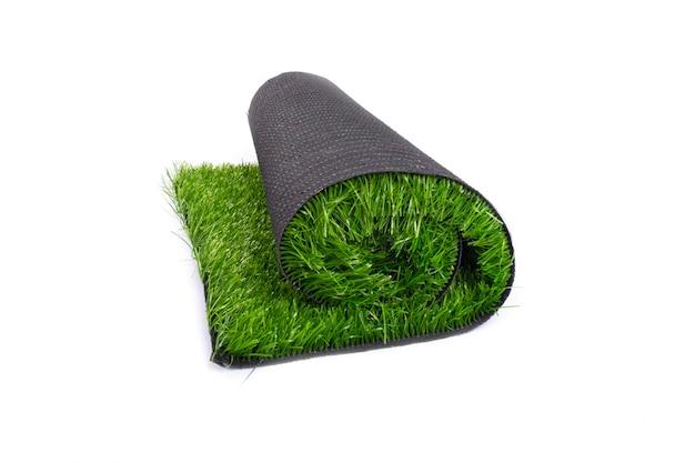 Rotolo di erba verde artificiale, moquette, tappeto erboso artificiale isolato su bianco