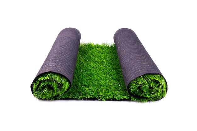 Rotolo di erba verde artificiale isolato su sfondo bianco, prato, copertura per campi sportivi.
