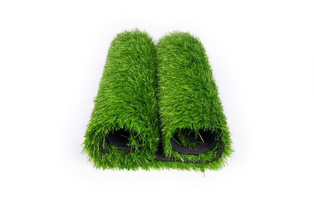 Rotolo di tappeto erboso artificiale isolato su priorità bassa bianca.
