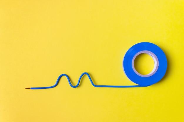 Rotolo di nastro adesivo di plastica blu e pezzo di filo elettrico su sfondo giallo. avvicinamento.
