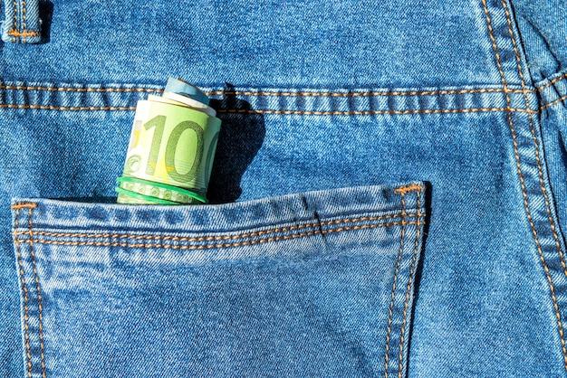 Rotolo di banconote in euro in una tasca dei jeans blu