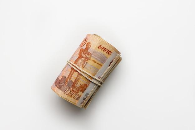 Un rotolo di cinquemila rubli russi. i rubli russi in banconote sono arrotolati su uno sfondo bianco. denaro e finanza in russia