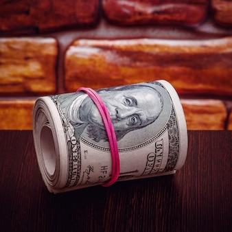 Un rotolo di banconote da cento dollari contro un muro di mattoni. avvicinamento.