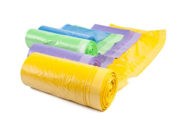 Rotolo delle isolato di plastica delle borse di immondizia su bianco