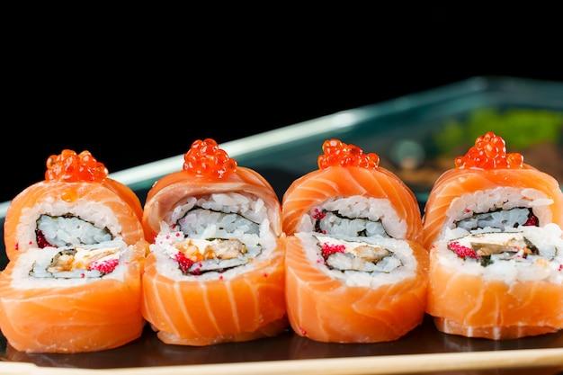 Rotolo drago rosso con salmone, caviale rosso, tobiko, anguilla, riso, primo piano nori. sushi cucina tradizionale giapponese.