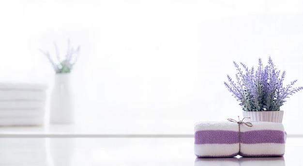 Rotolo di asciugamano spa legato con corda di canapa sul bancone bianco.