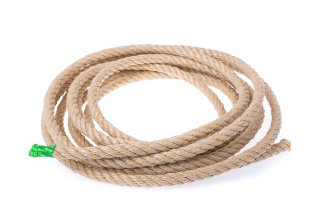 Un rotolo di materiale robusto in corda. contorto in un cerchio. su un muro bianco
