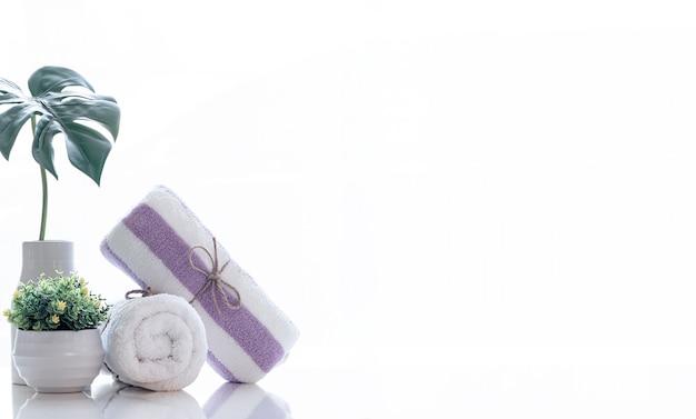 Rotolo di asciugamano spa bianco legato con corda di canapa sul bancone bianco.