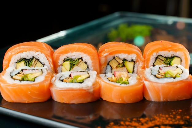 Rotolo con salmone, anguilla, avocado, granchio, primo piano di cipolla verde. cucina tradizionale giapponese.