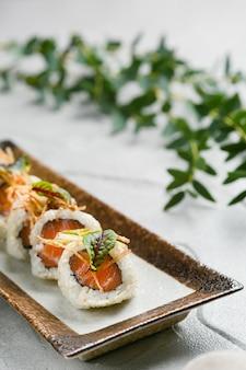 Rotoli con salmone e microgreen sul primo piano del piatto ceramico con lo spazio della copia