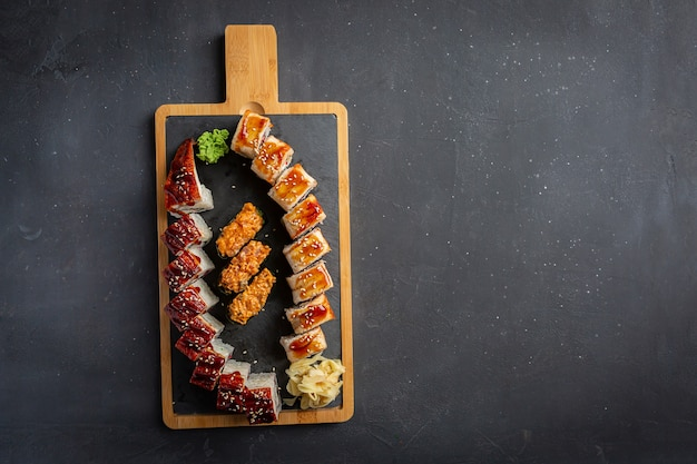 Rotolo con anguilla affumicata, formaggio e rucola. impostare il rotolo di sushi. cucina tradizionale giapponese. isolato su nero.