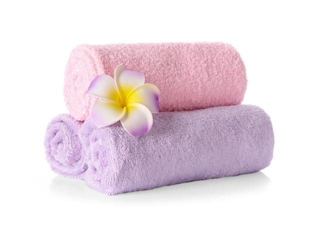 Asciugamani morbidi e puliti arrotolati con fiore su priorità bassa bianca