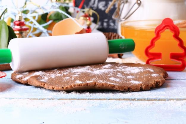 Impasto steso per dolci fatti in casa di natale con pan di zenzero su uno sfondo di legno chiaro messa a fuoco morbida selettiva in stile rustico