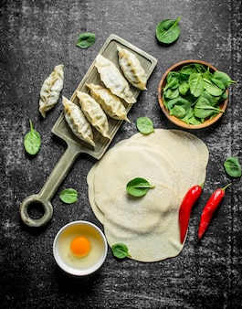 Pasta stesa per preparare gnocchi di gedza crudi fatti in casa sul tavolo rustico scuro