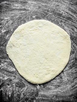 Pasta per pizza stesa. su fondo rustico