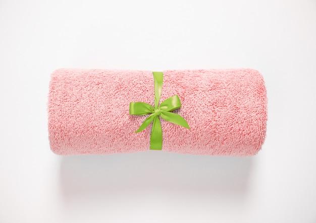 Asciugamano di spugna rosa arrotolato legato da nastro verde su uno sfondo bianco. vista dall'alto.