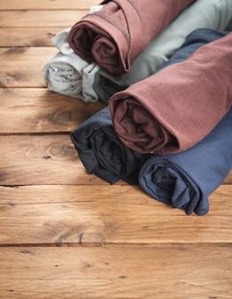 Magliette rotolate su fondo di legno