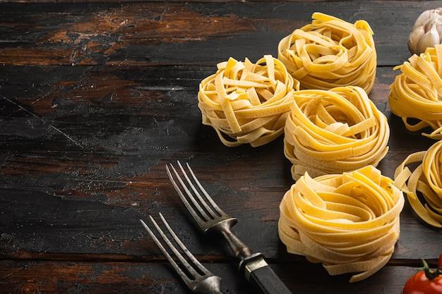 Forma di tagliatelle arrotolate di pasta italiana con set di ingredienti, sul vecchio tavolo in legno scuro