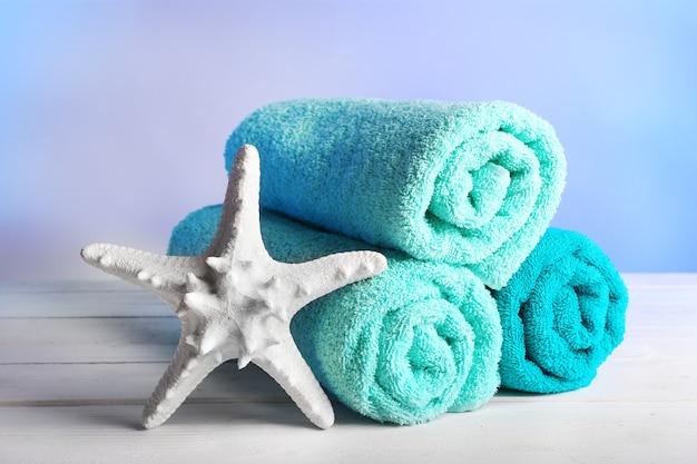 Asciugamani arrotolati con stelle marine su un tavolo di legno e colorato chiaro