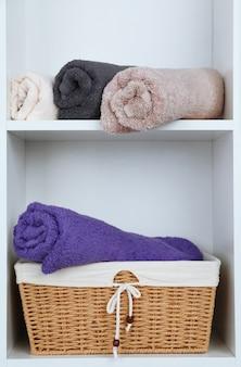 Asciugamani arrotolati con cesto di vimini sullo scaffale di sfondo rack