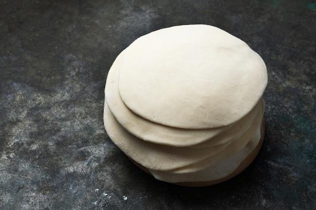 Pasta cruda arrotolata per chapati con focaccia indiana. pronto per cucinare il concetto. pasti facili. cucina casalinga. avvicinamento