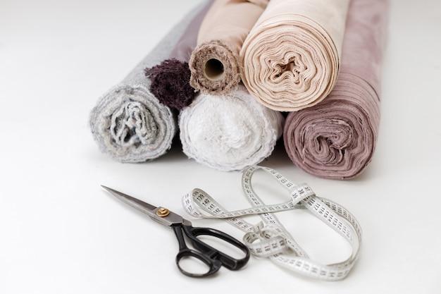 Forbici di stoffa arrotolate e centimetro sul tavolo bianco della sarta