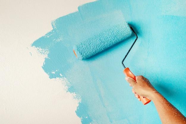 Verniciatura a pennello a rullo, operaio che dipinge sulla superficie della parete pittura appartamento, ristrutturando con vernice di colore blu.