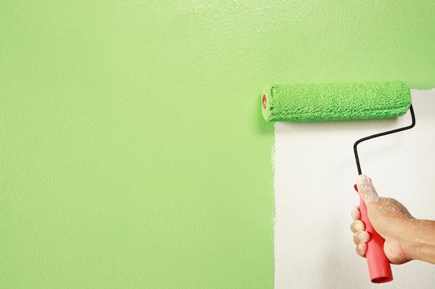 Verniciatura a pennello a rullo, operaio che dipinge sulla superficie dell'appartamento pittura murale, ristrutturando con vernice di colore verde.
