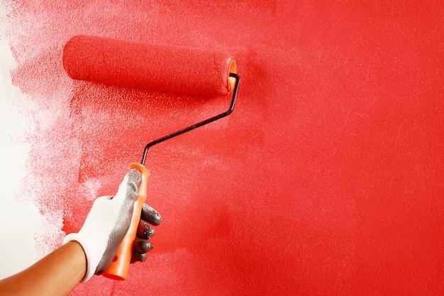 Verniciatura a pennello a rullo, operaio che dipinge sulla superficie della parete pittura appartamento, ristrutturando con vernice di colore rosso.