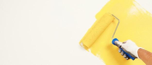 Pittura a pennello a rullo, pittura dell'operaio sulla superficie dell'appartamento di pittura murale, ristrutturazione con vernice di colore giallo