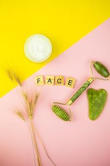 Rullo in giada di quarzo verde su fondo rosa-giallo. lay piatto