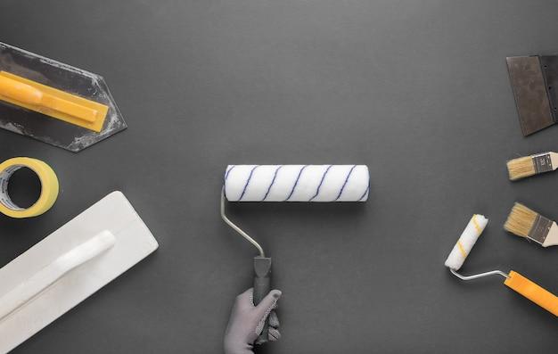 Rullo per dipingere in una mano guantata e altri strumenti per la riparazione