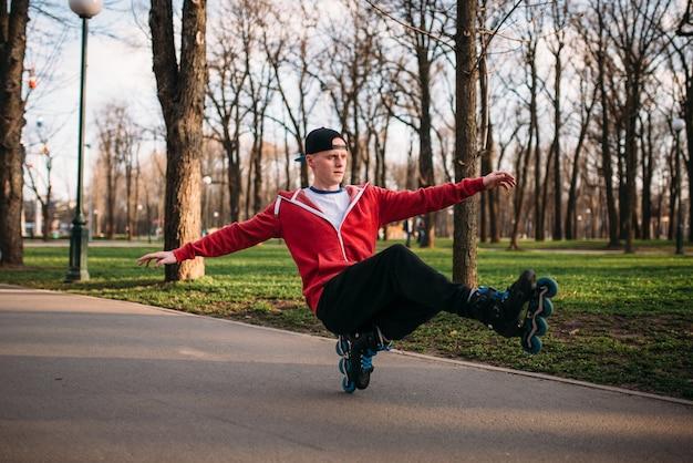 Roller skater facendo esercizio di equilibrio sul marciapiede nel parco cittadino. tempo libero pattinatore maschile